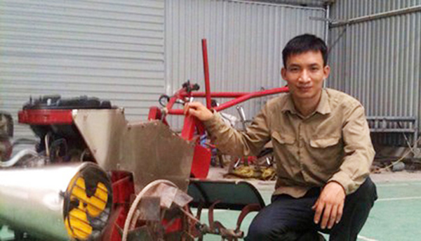 Anh Tạ Đình Huy bên chiếc máy nông nghiệp đa chức năng do anh sáng chế.
